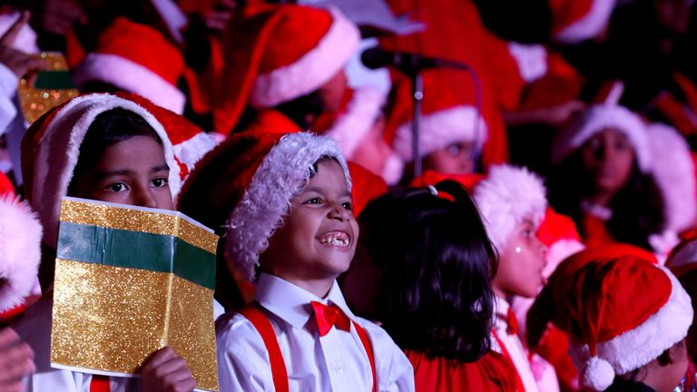 Children wearing Santa Claus caps react as they perform Christmas carols at the premises of the St. Patrick's Cathedral in Karachi, Pakistan December 22, 2018
