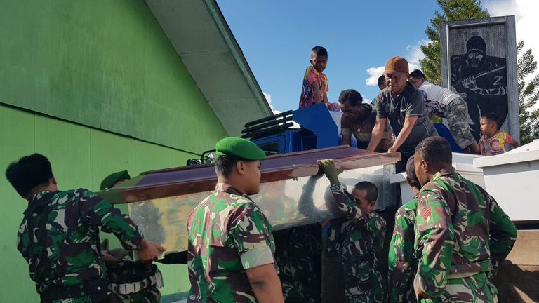 Indonesian soldiers prepare coffins for construction workers who were killed