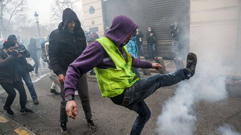 A 'yellow vest' protester clashes with police near the Champs Elysees