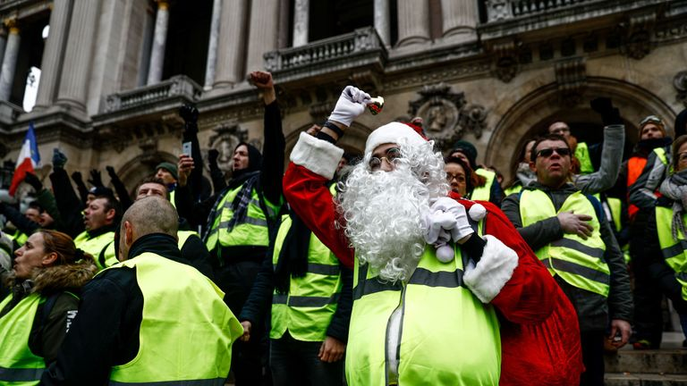 A protester dressed as Santa Claus on the steps of the Opera Garnier