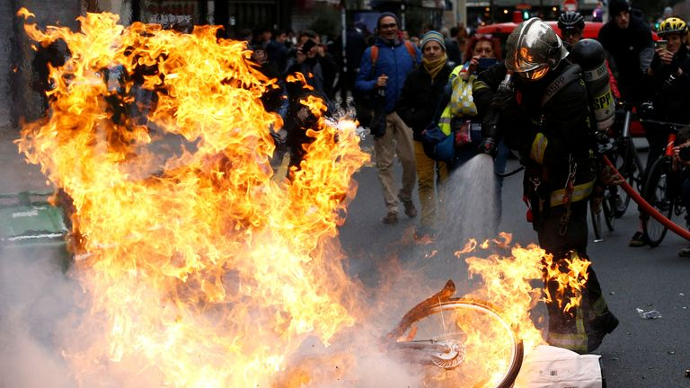 A fireman extinguishes a burning bicycle during clashes