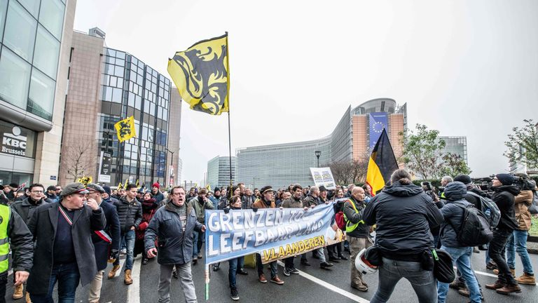 People wave the flag of the Flanders as they take part in a gathering called by the right-wing Flemish party Vlaams Belang and other organisations, in Brussels, on December 16, 2018 to protest against the UN Marrakech global pact on migration signed last week by Belgian Prime Minister. - Brussels mayor forbade the venue of this march but State council ruled against that decision and the mach is wel authorized. A counter march is also organised for a solidary Belgium.