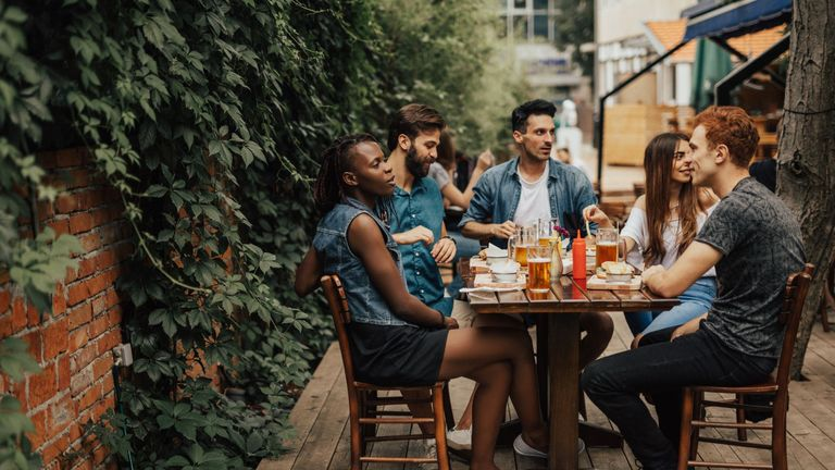 Happy multi-ethnic group of people sitting at the fastfood restaurant - Stock image