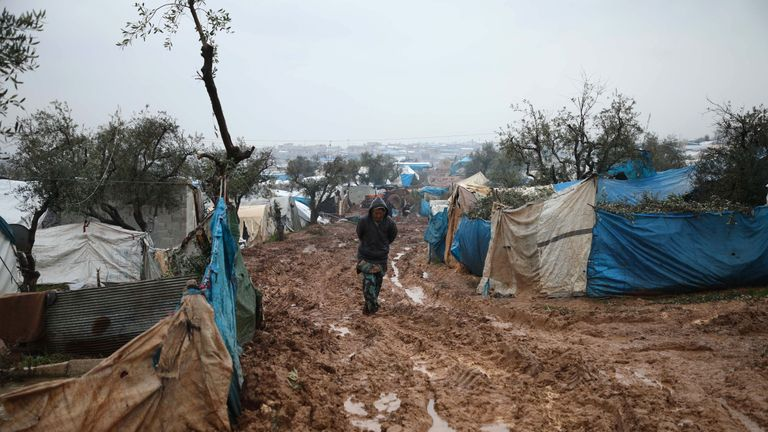 Syrian displaced people walk in a flooded camp near Kah, in the Idlib province, northeastern Syria,