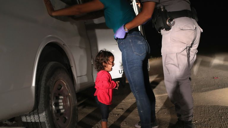 A two-year-old Honduran asylum seeker cries as her mother is searched and detained near the U.S.-Mexico border