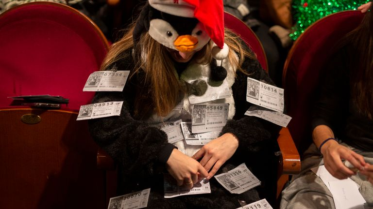 A spectator dressed as a penguin sticks duplicates of lottery tickets to her costume at the draw