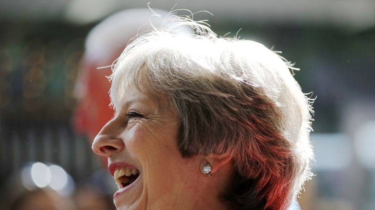 British Prime Minister Theresa May laughs during a visit to the Royal Welsh Show in July 2018