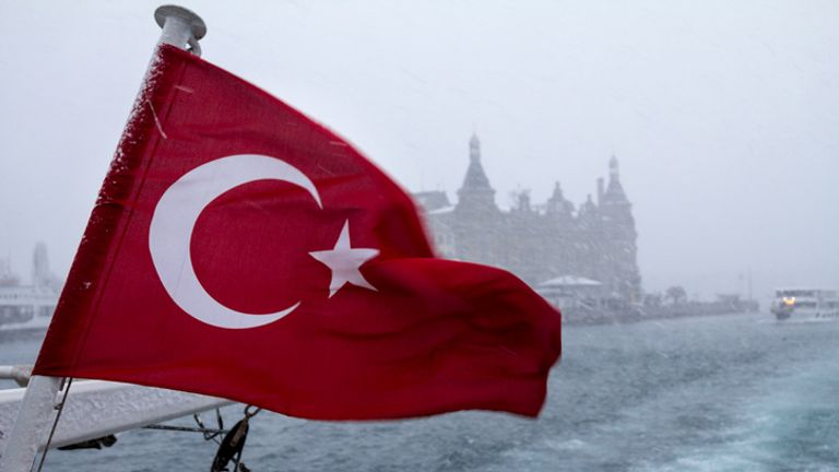 Turkish flag on a ship during a snowstorm, a Europe-Asia ferryboat can be seen in the background, as well as the Haydarpasa train station..Picture of a on Europe Asia lines under an unusual snowstorm over Istanbul with a Turkish flag on the foregroun