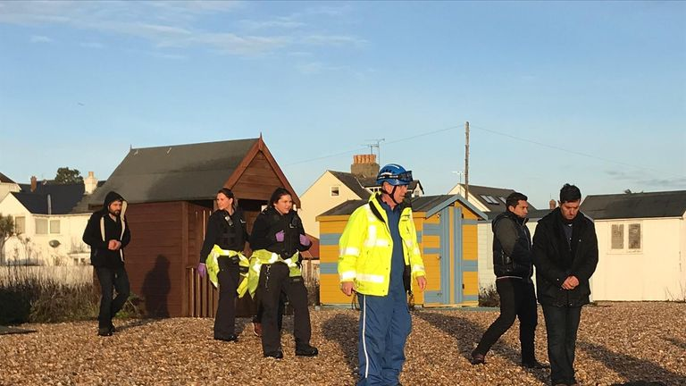 Border officials with suspected migrants on the beach at Kingsdown, Kent