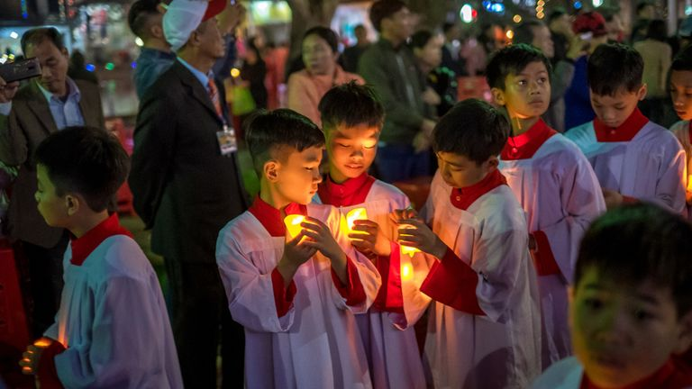 Pilgrims and locals take part in the procession of Baby Jesus led by Bishop Joseph Nguyen Nang during the Christmas Midnight Mass on the site of Phat Diem Cathedral on December 24, 2018 in Kim Son District, Ninh Binh Province, Vietnam