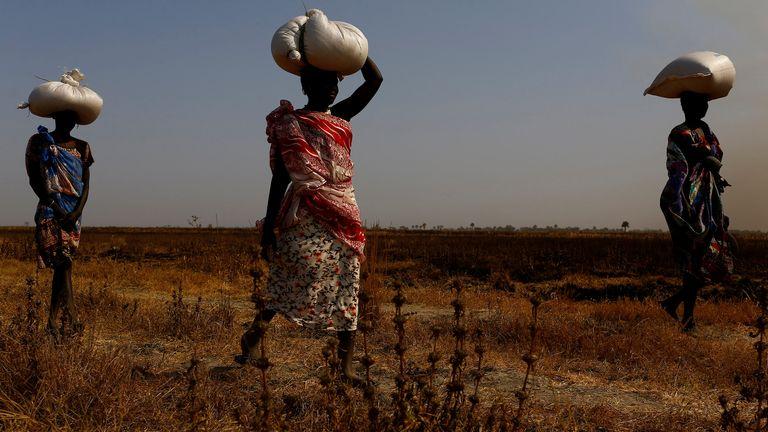 Women carry sacks of food in Thonyor, Leer State, South Sudan,