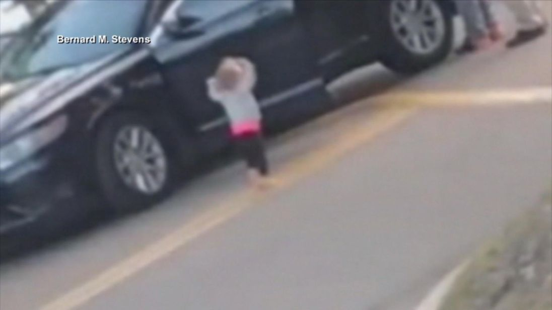 Barefoot Toddler Walks with Hands Raised Towards Armed Cops