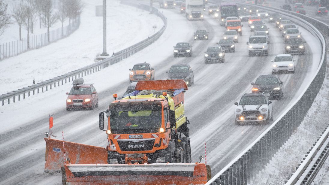 A snow plough clears the A9 highway in Garching southern Germany