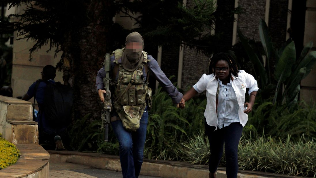 A security agent evacuates an injured woman from the scene