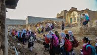 Students walk through a damaged road on their way back from school in Mosul