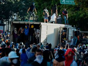 A vehicle is overturned as opposition demonstrators block a freeway