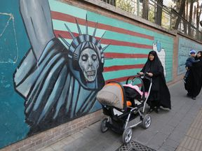 Iranian women walk past landmark graffiti on the walls of the former US embassy in Tehran during a protest on November 4, 2018, marking the anniversary of its storming by student protesters that triggered a hostage crisis in 1979. - Thousands joined rallies in Tehran and other Iranian cities, carrying placards that mocked President Donald Trump, wiping their feet on fake dollar bills, and engaging in the usual ritual of burning the US flag. (Photo by ATTA KENARE / AFP) (Photo credit should read