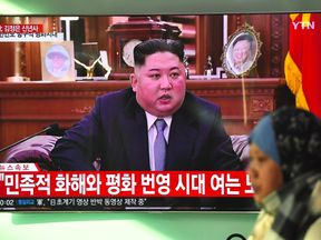 A woman walks past a television news screen showing a New Year speech by North Korean leader Kim Jong Un at a railway station in Seoul on January 1, 2019