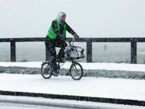 A man cycles through the snow in Whitley Bay, North Tyneside