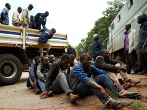 People arrested during protests wait to appear at magistrates' court in Harare