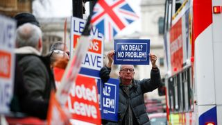 Pro-Brexit demonstrators hold signs outside the Houses of Parliament
