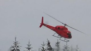 Authorities in Germany use helicopter to remove heavy snow from trees at side of road