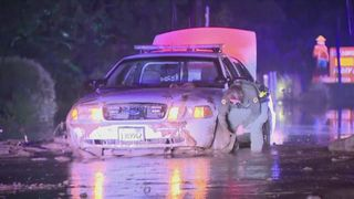 Police officer digging car out of the mud.