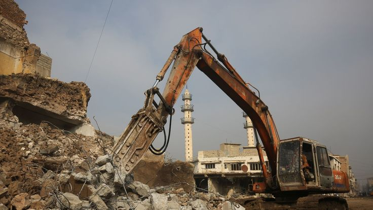 A digger is used to clear rubble in Mosul in December 2018 after destruction caused by the war with Islamic State