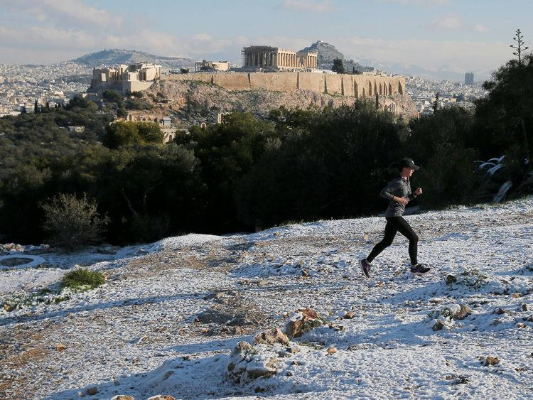 A man jogs up Filopappou Hill opposite the Acropolis in Athens