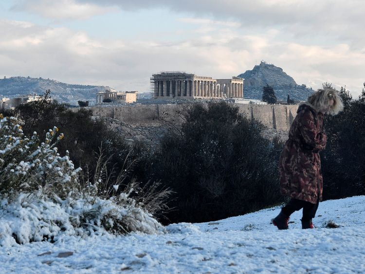 A woman walks at Athens central Filippapou hill overlooking the ancient Acropolis, after a snowfall over the Greek capital