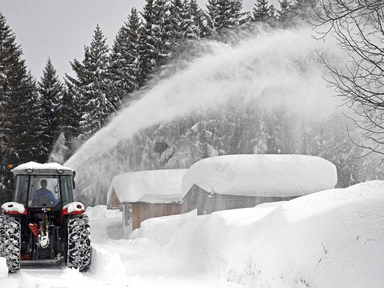 A snow plough clears Ramsau am Dachstein, Austria where five foot of snow has fallen