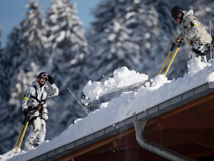 German Bundeswehr soldiers remove snow from the roof of the Watzmann Therme on January 11, 2019 in Berchtesgaden, Germany