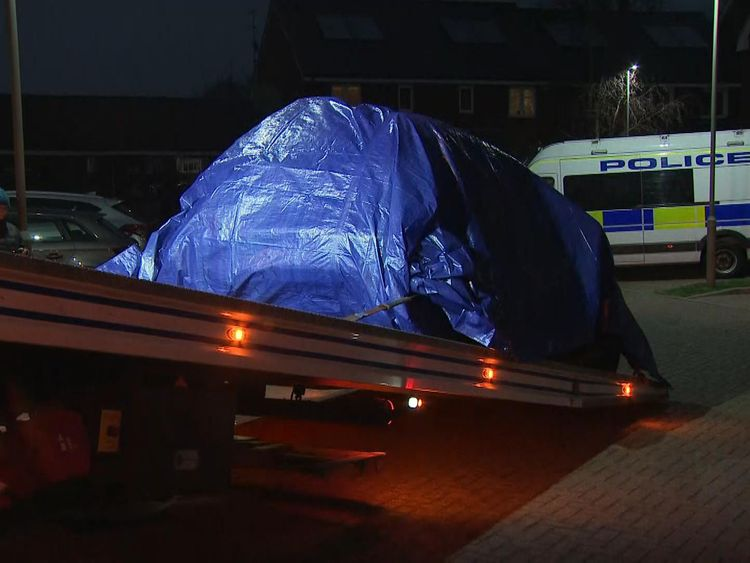A car is towed away by police outside the residence raided by police