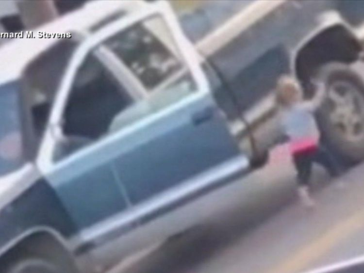 Barefoot toddler walks toward police with hands up while imitating arrested father