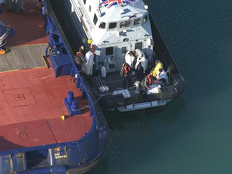 The suspected migrants were wrapped in blankets after disembarking their dinghy