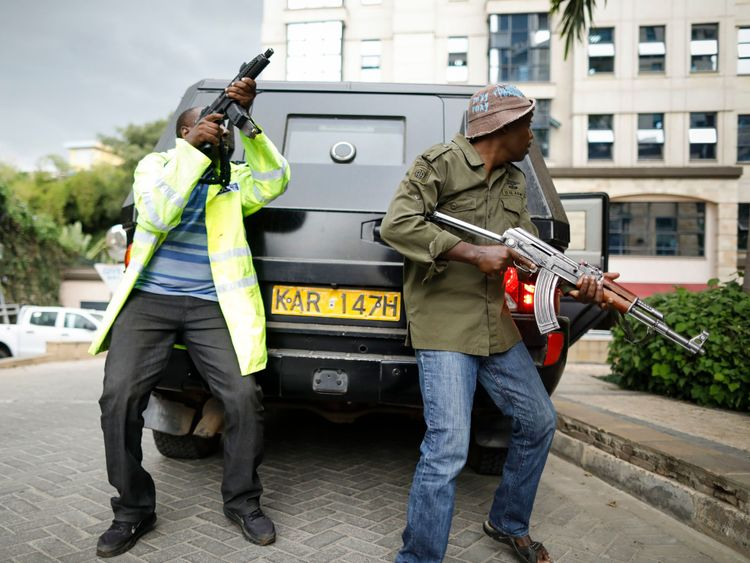 Kenyan security officers take cover behind a moving vehicle as they search for attackers