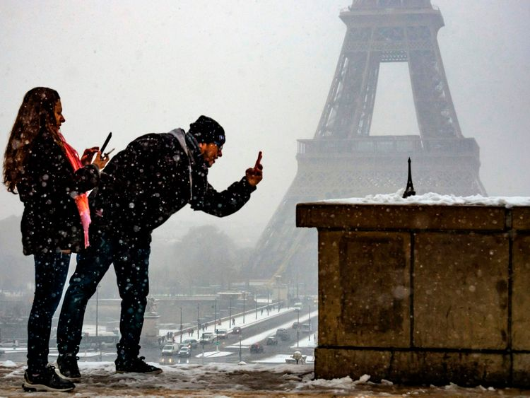 A tourist takes advantage of the snow to take a picture of his mini Eiffel Tower