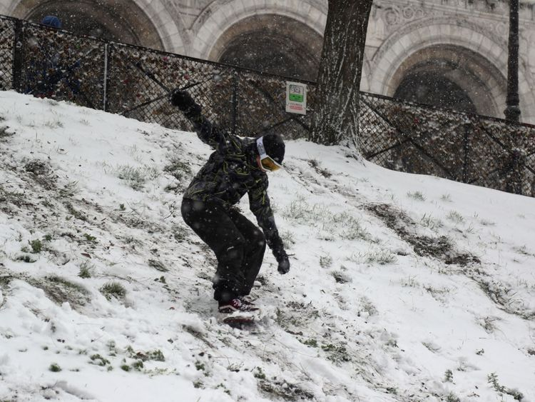 A man rides snowboard on the Butte Montmartre in Paris