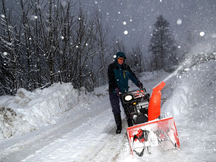 A man removes snow from a road during heavy snowfall in Eisenerz Austria