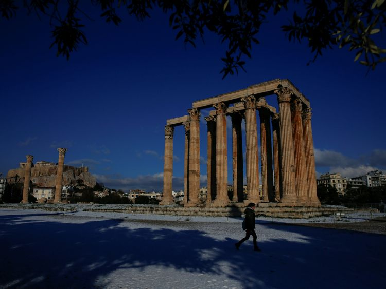 A visitor at the ancient Temple of Zeus in Athens after snow fell there
