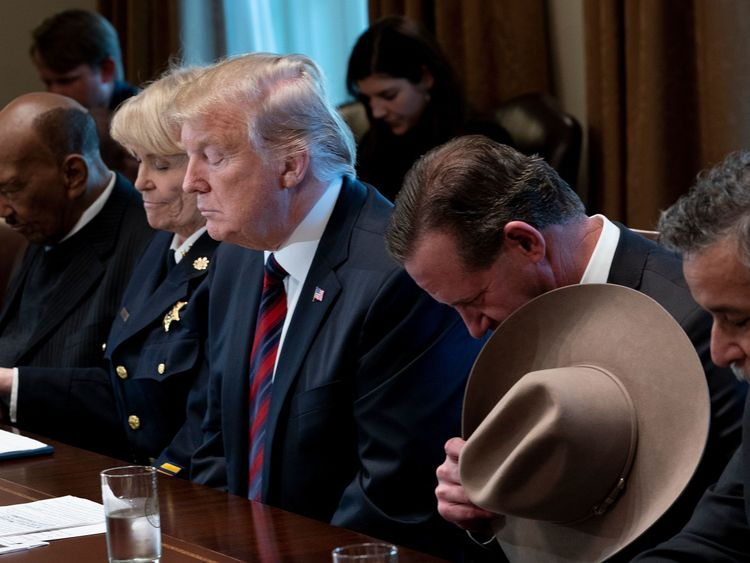 US President Donald Trump and others listen to a prayer during a meeting about border security in the Cabinet Room of the White House