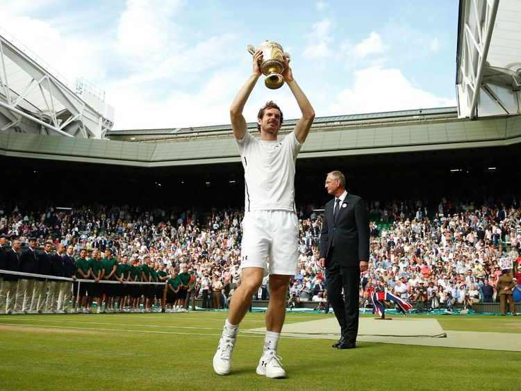 Britain's Andy Murray poses with the winner's trophy after his men's singles final victory over Canada's Milos Raonic on the last day of the 2016 Wimbledon Championships