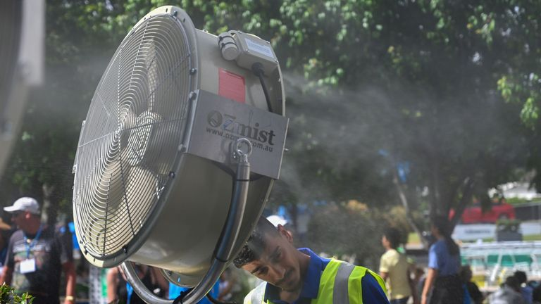A man cools down in front of a mist fan for relief from the hot weather on day 12 of the Australian Open tennis tournament in Melbourne