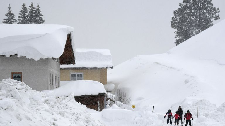 Skiers make their way through the streets after heavy snowfall in Filzmoos