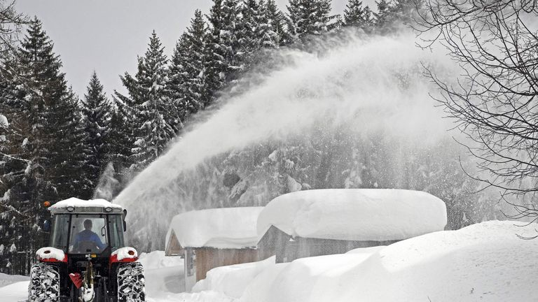 A snow plough clears Ramsau am Dachstein, Austria where five foot of snow has fallen