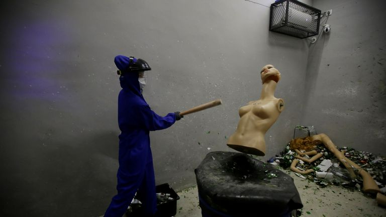 A woman smashes a mannequin to release some anger