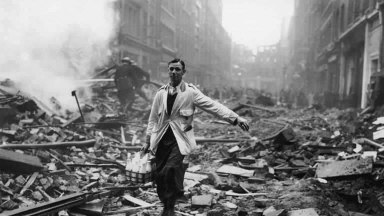 A milkman delivering milk in a London street devastated during a German bombing raid. Firemen are dampening down the ruins behind him