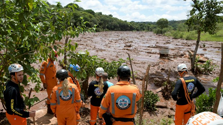 Rescue workers are seen after a dam, owned by Brazilian miner Vale SA, burst
