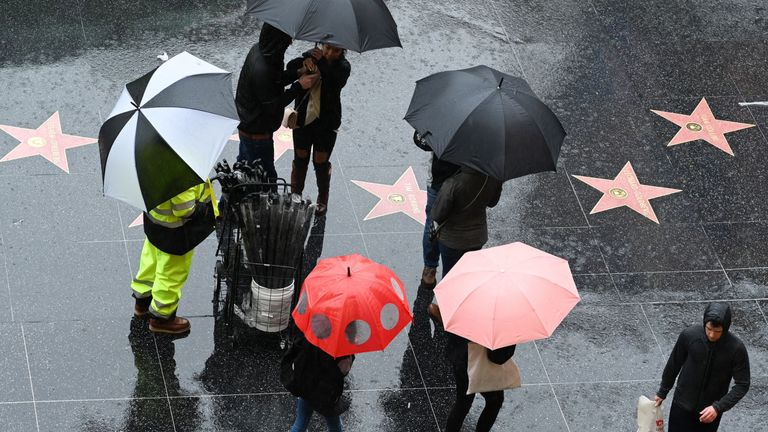 A vendor sells umbrellas in Hollywood, California January 14, 2019. - A storm over Southern California delivered rain and snow, heightening the threat of mud and debris flows in areas scarred by recent wildfire. Rain is expect to continue for next three days. (Photo by Robyn Beck / AFP) (Photo credit should read ROBYN BECK/AFP/Getty Images)