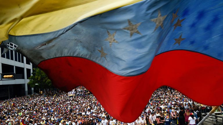 A Venezuelan national flag flutters during a mass opposition rally against President Nicolas Maduro in which Venezuela's National Assembly head Juan Guaido (out of frame) declared himself the country's 'acting president', on the anniversary of a 1958 uprising that overthrew a military dictatorship, in Caracas on January 23, 2019